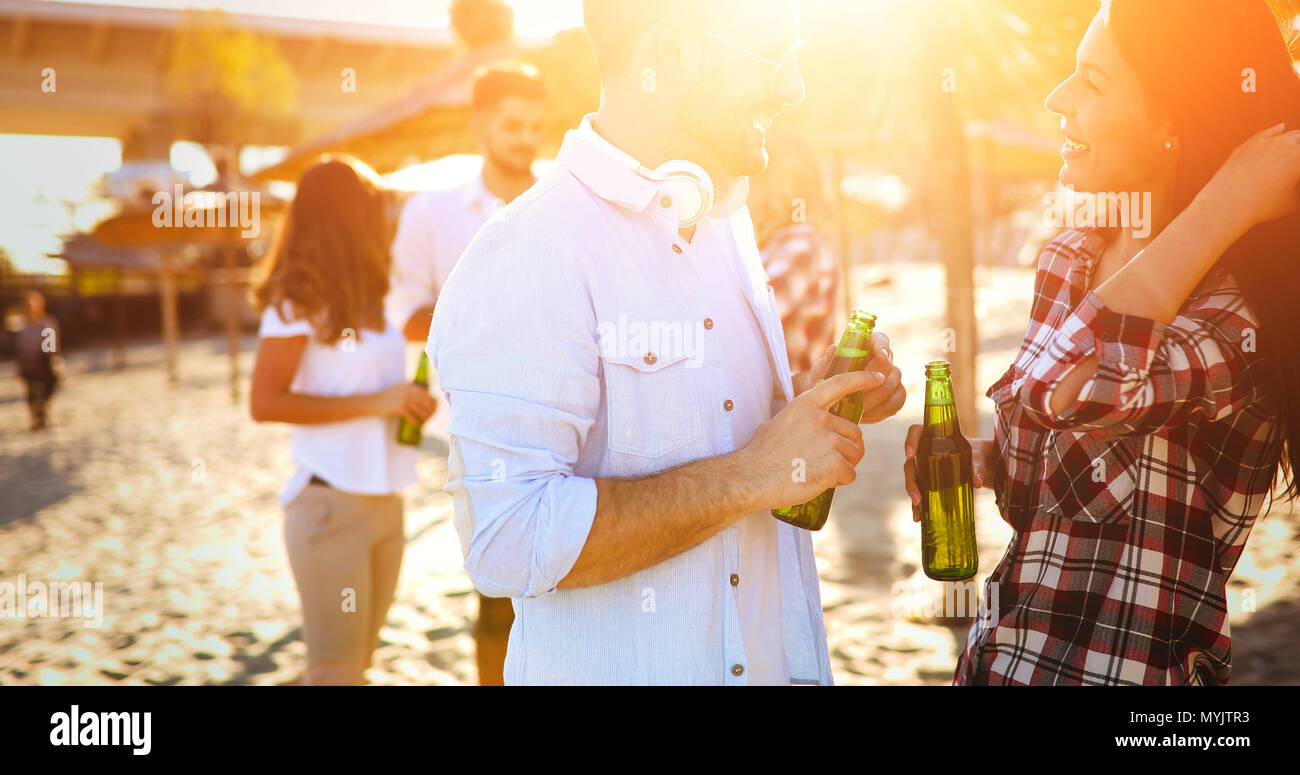 Friends partying and having fun on beach at summer - Stock Image