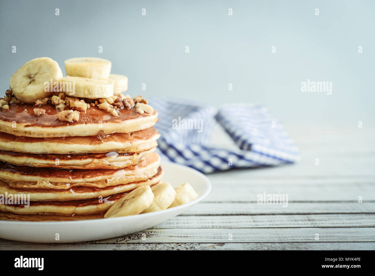 Pancakes with banana,walnut and muple syrup for a breakfast on wooden background closeup Stock Photo