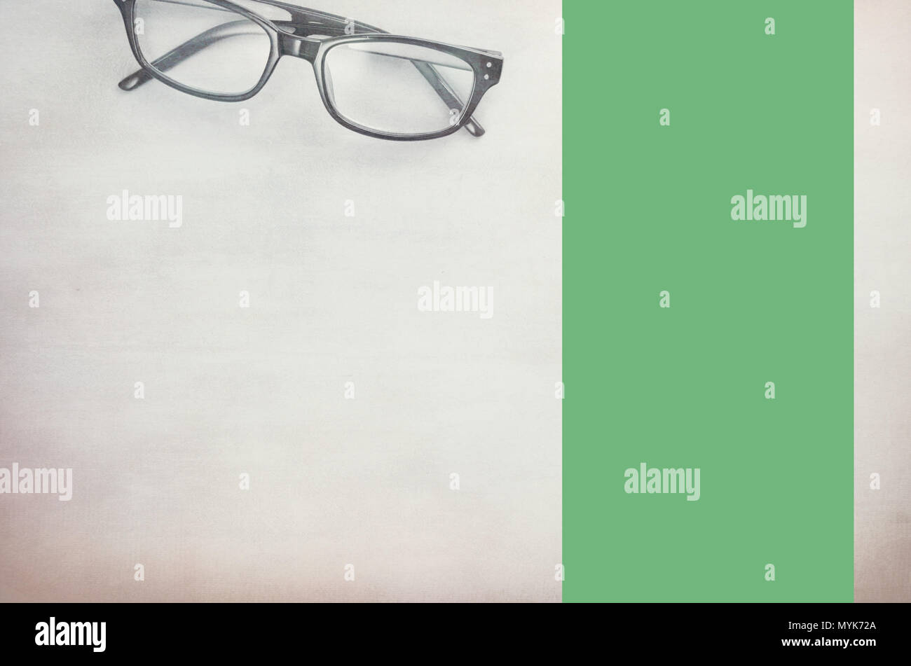pair of framed eyeglasses on a light textured surface - directly above Stock Photo
