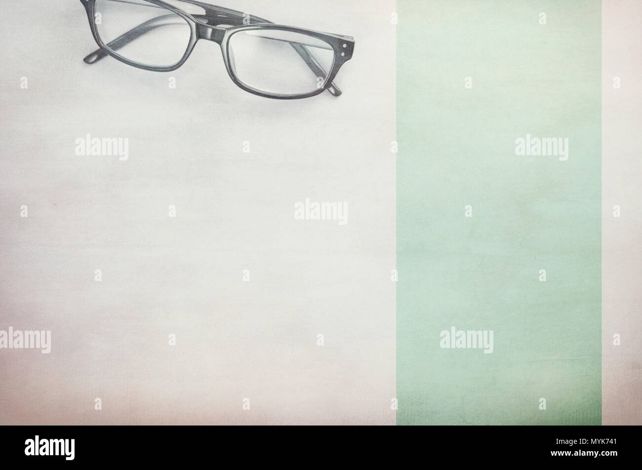 pair of framed eyeglasses on a light textured surface - directly above - Stock Image
