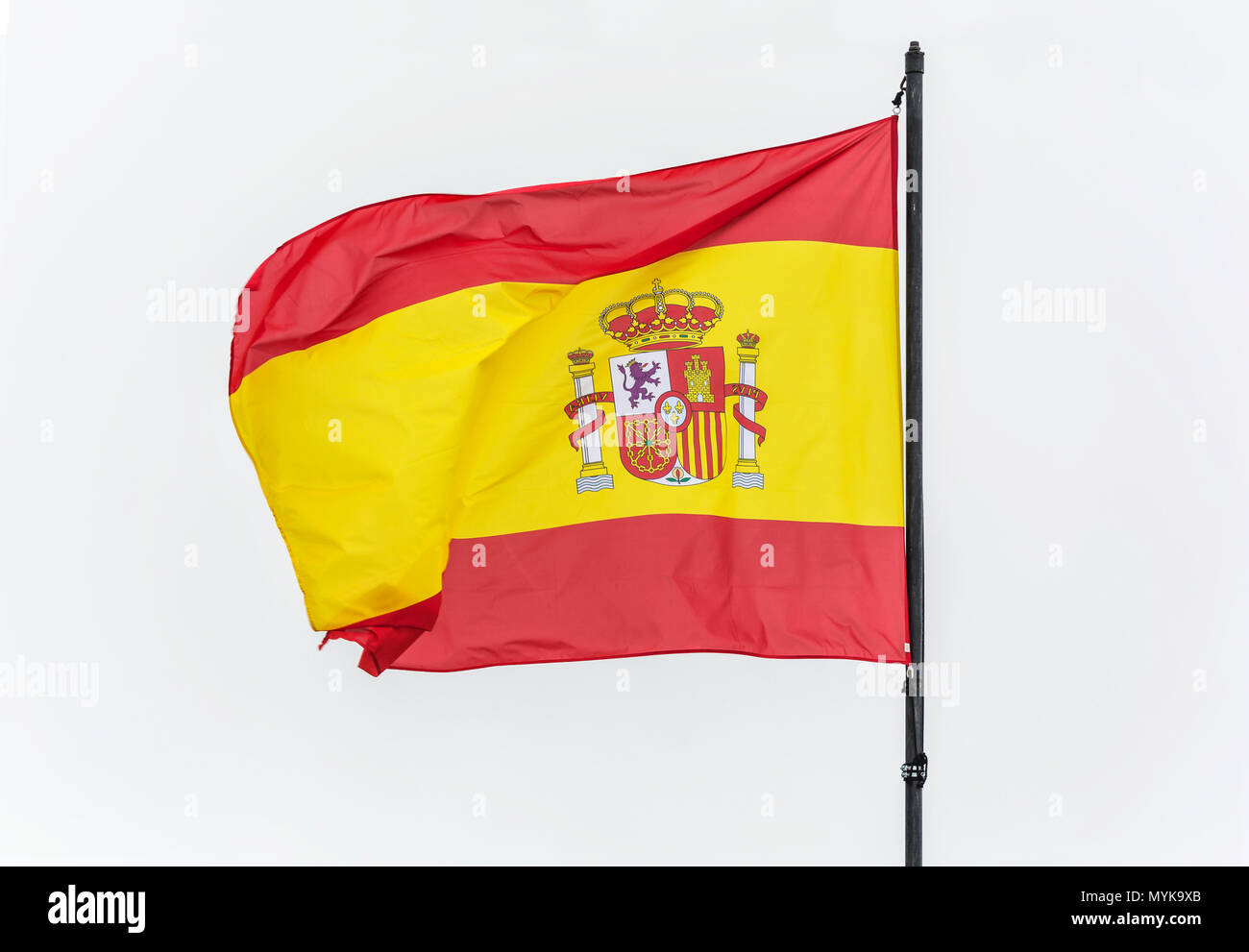 Spain flag on the flagpole on the bright background of the sky flutters in the wind - Stock Image