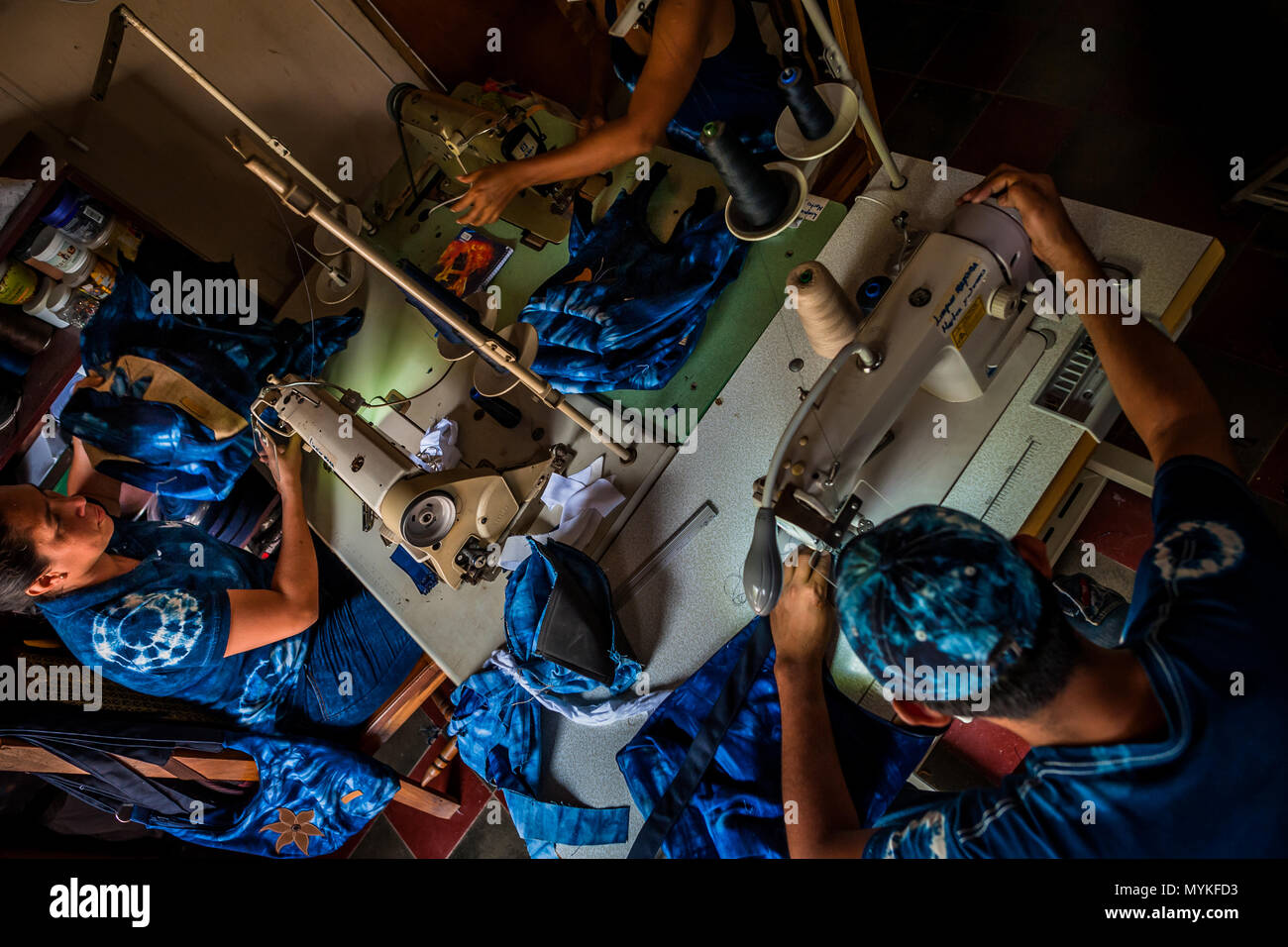 Salvadoran seamstresses sew indigo-dyed tote bags on the sewing machines in an artisanal clothing workshop in Santiago Nonualco, El Salvador. - Stock Image