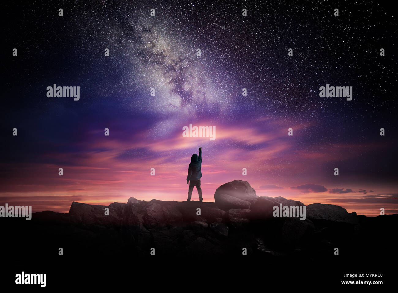 Night time long exposure landscape photography. A man standing in a high place reaching up in wonder to the Milky Way galaxy, photo composite. - Stock Image
