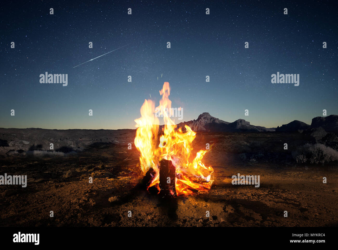 Exploring the wilderness in summer. A glowing camp fire at dusk providing comfort and light to appreciate nature, good times and the night sky full of - Stock Image