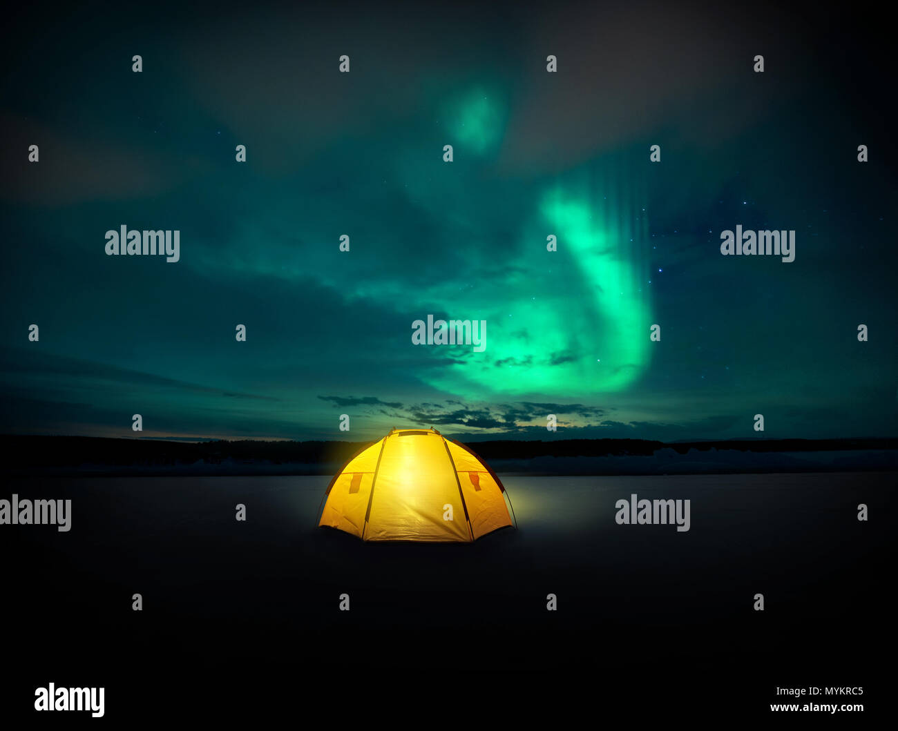Out in the wilderness The Norther lights ( Aurora Borealis) dances across the night sky in Sweden, above the glowing lights from the camping tent. Pho - Stock Image
