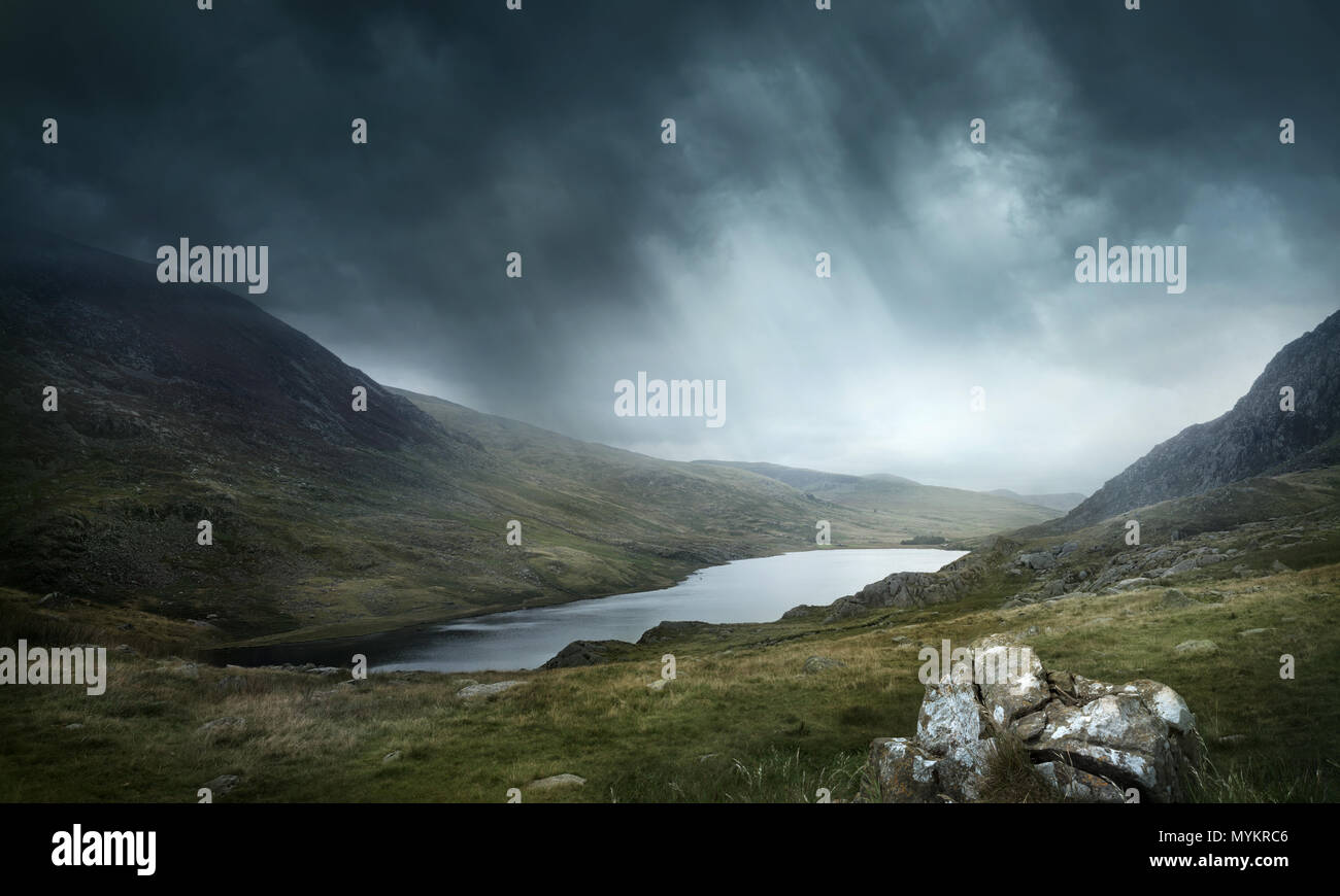 A place of myths and legends. Wild weather and terrain make for good adventures. Mountains and lakes landscape. Photo composite. - Stock Image