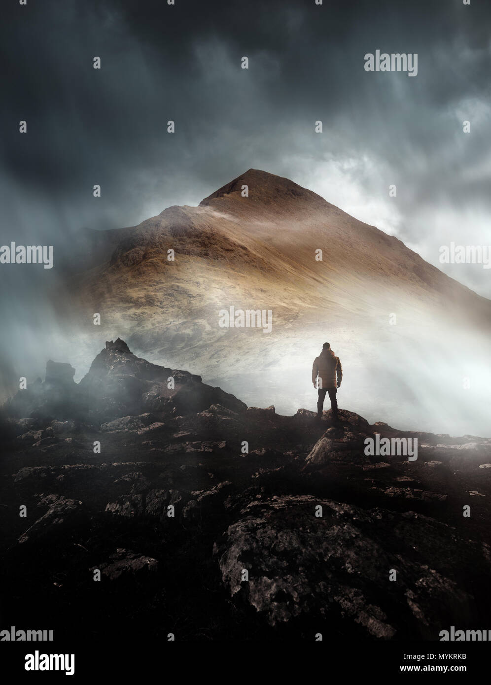 A person hiking looks onwards at a mountain shrouded in mist and clouds with the peak visible. Scenic landscape photo composite. - Stock Image