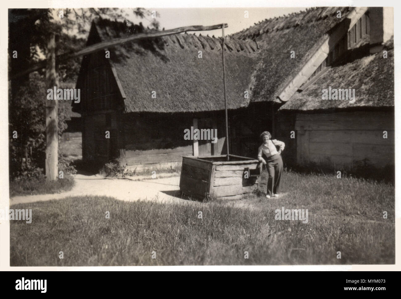 Woman poses by an old-fashioned counterbalance well by a thatched farmhouse near Odense on the island of Funen, Denmark.  Photograph made circa 1946 Stock Photo