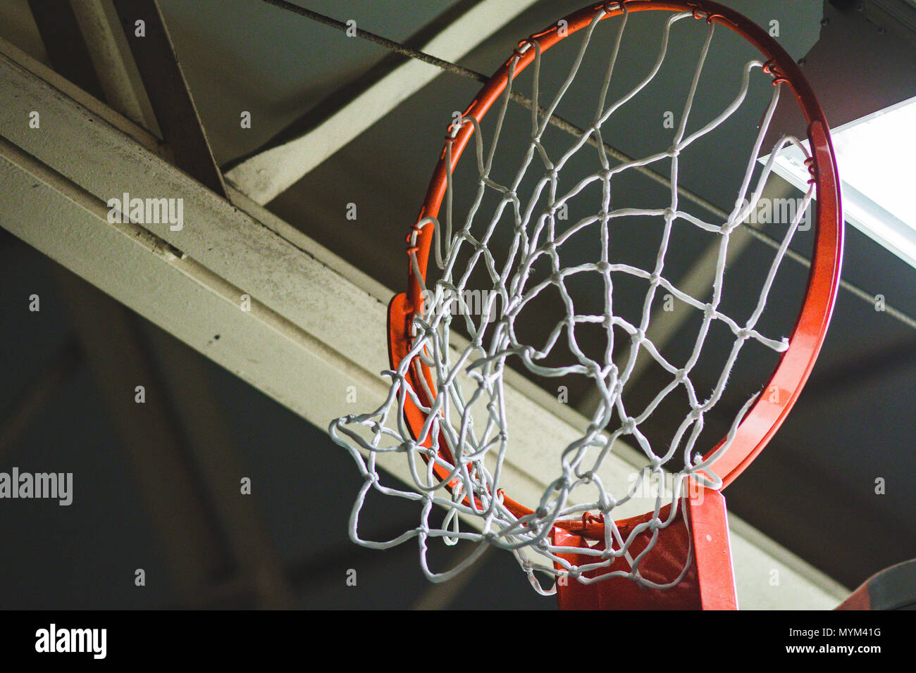 a basketball hoop and net retracted up for storage - Stock Image