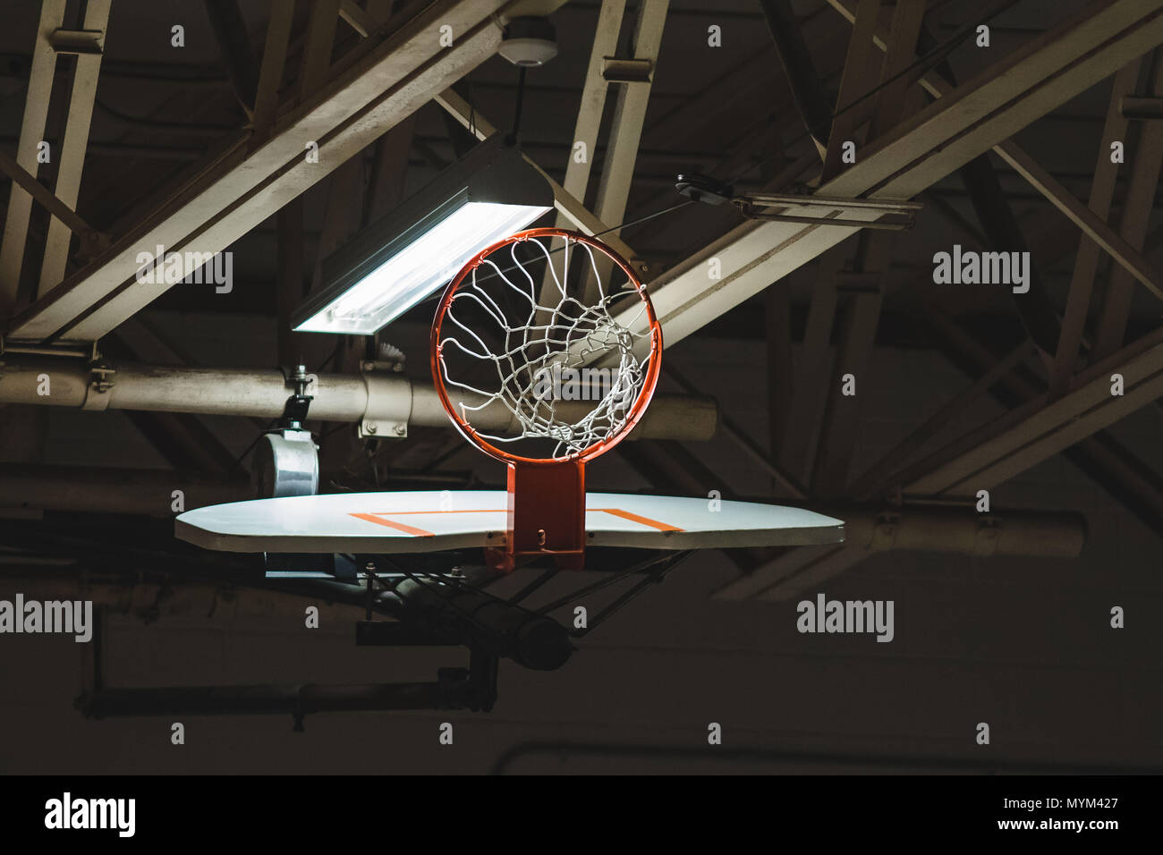 a basketball backboard hoop and net retracted up for storage - Stock Image