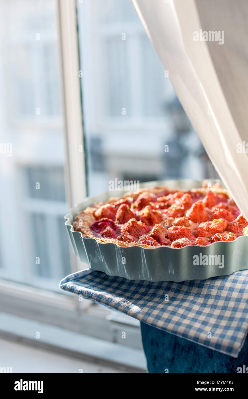 Open cake with strawberries in blue bowl for breakfast, near the window and daylight. Homemade baking. Free space for text. Copy space - Stock Image