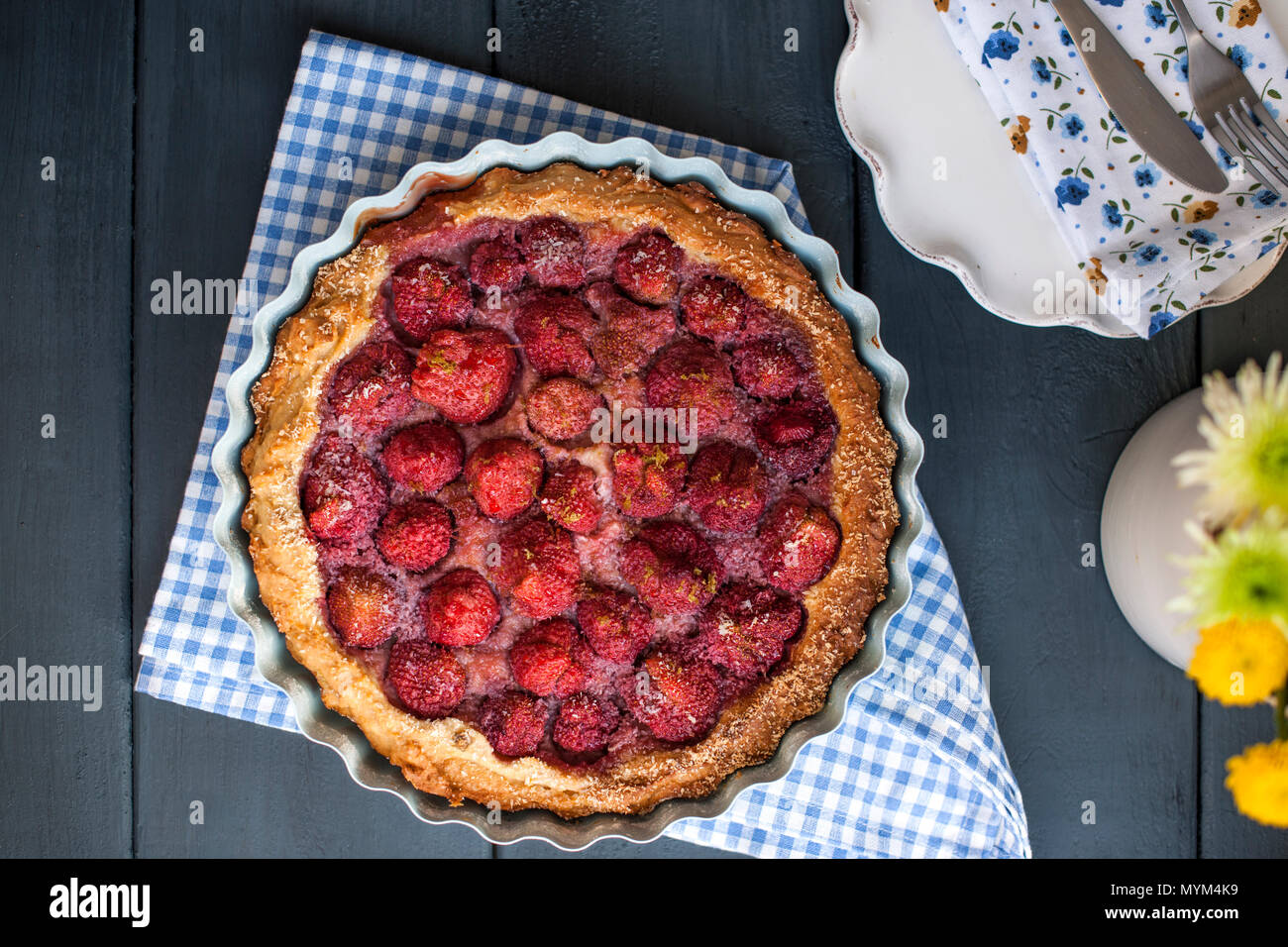 Open cake with strawberries in blue bowl for breakfast, on a black wooden background. Homemade baking. Free space for text. Copy space . Flat lay. - Stock Image