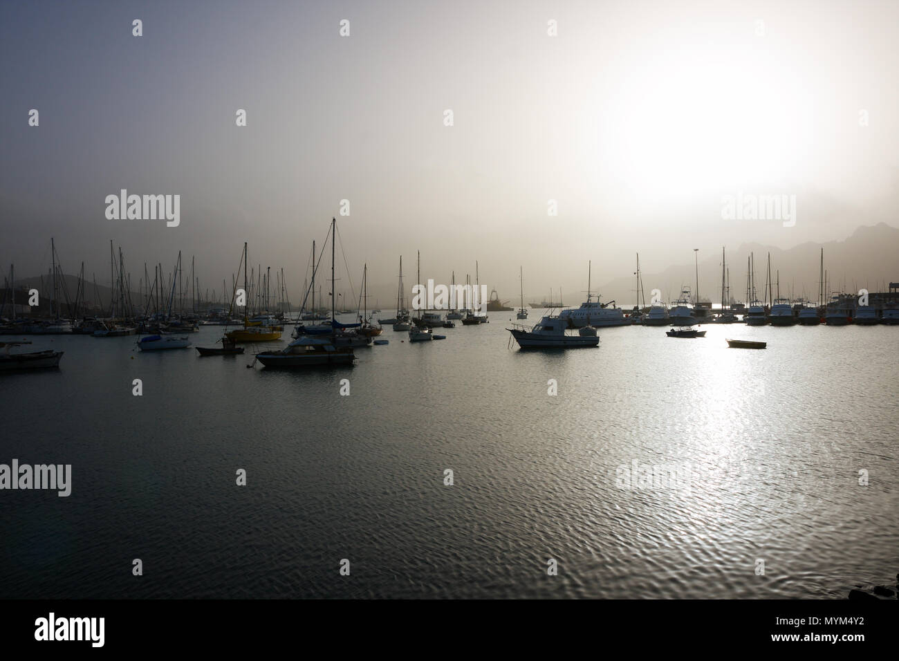 MINDELO, CAPE VERDE - DECEMBER 07, 2015: Boats and yachts in port of Sao Vicente island in bright light of the misty sunset Stock Photo