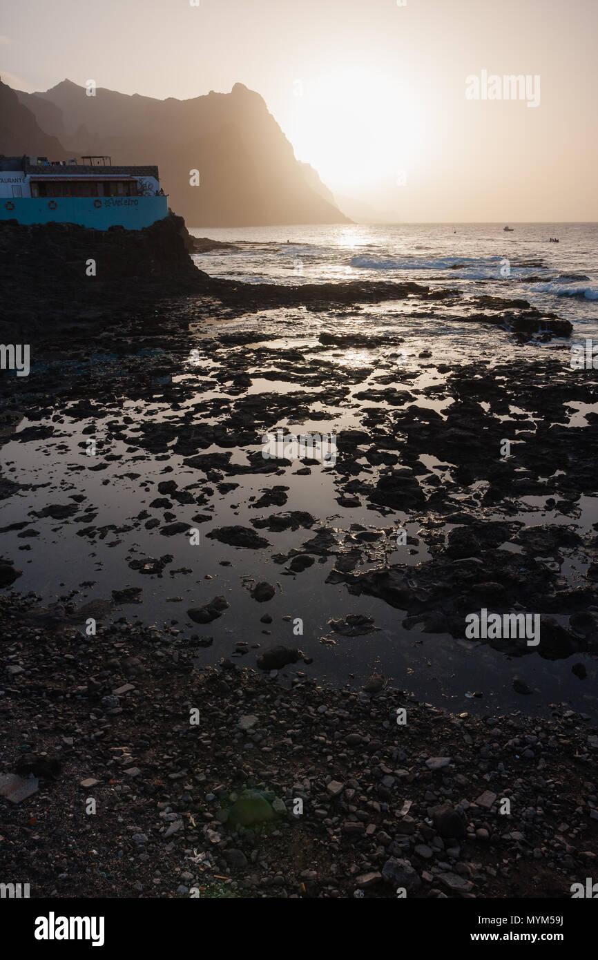 PONTA DO SOL, CAPE VERDE - DECEMBER 08, 2015: Beautiful sunset evening at the rocky shore of Santo Antao Island. Veleiro restaurant, mountains and the Stock Photo