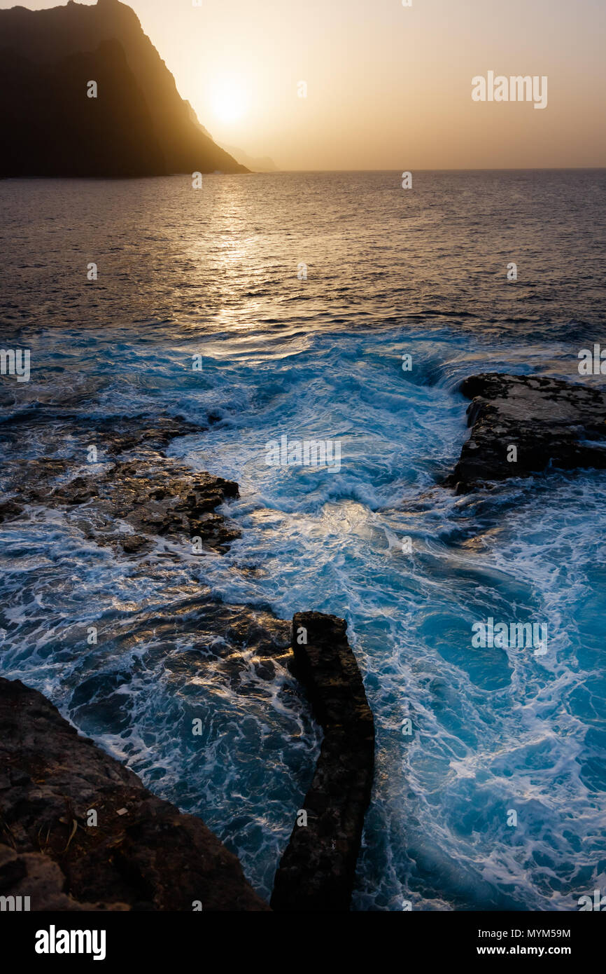 Dusty sunset and turbulent waves at the rocky beach of Santo Antao Island Stock Photo