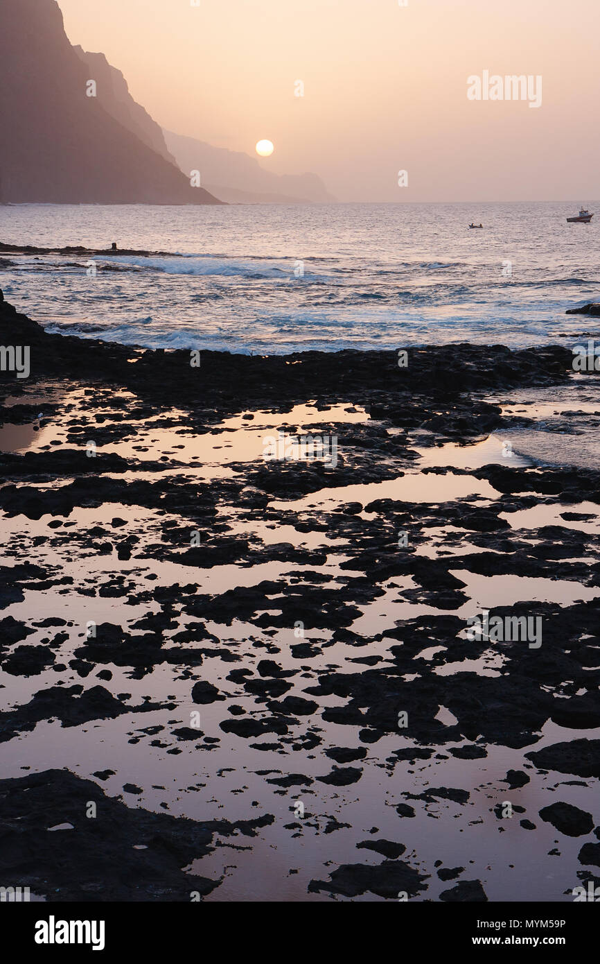 Cape Verde sunset at the rocky beach of Santo Antao Island. Mountains at the ocean Stock Photo