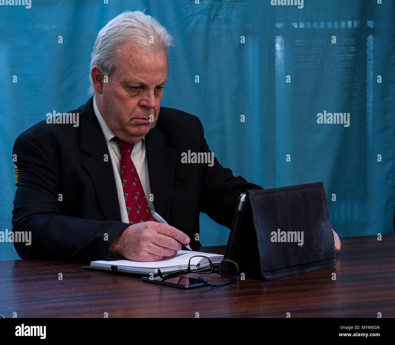 Elderly caucasian executive with grey hair and a dark suit works at a boardroom table image with copy space in landscape format - Stock Image