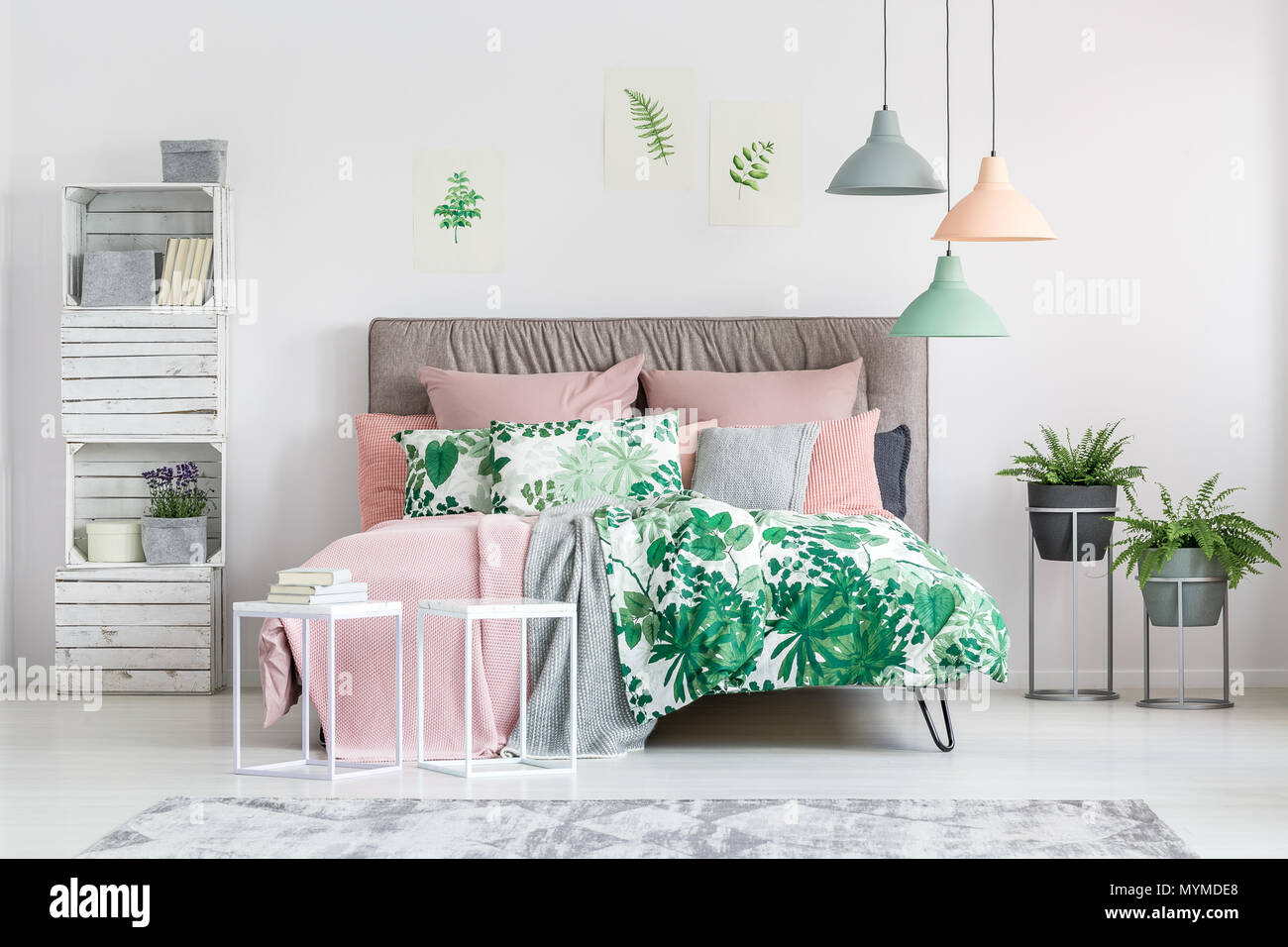 White pallet chest bookcase with books, flowers and boxes in stylish bedroom with potted plants - Stock Image