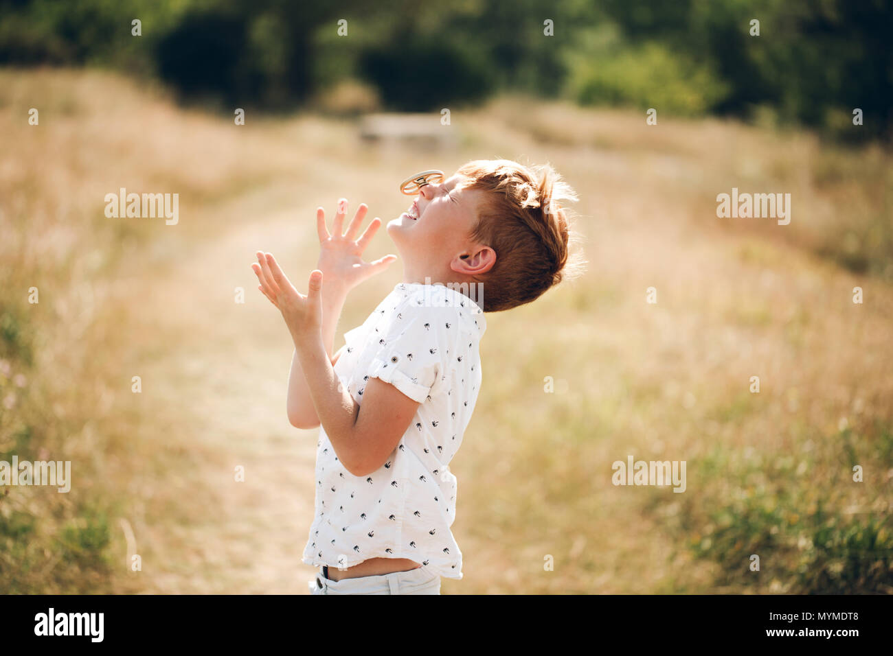 Boy is spinning fidget spinner on his nose - Stock Image