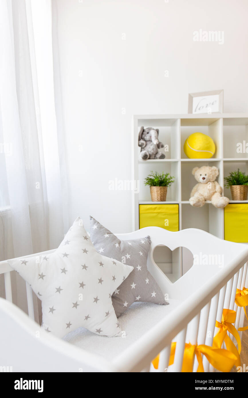 Shot of a white crib in a nursery room - Stock Image