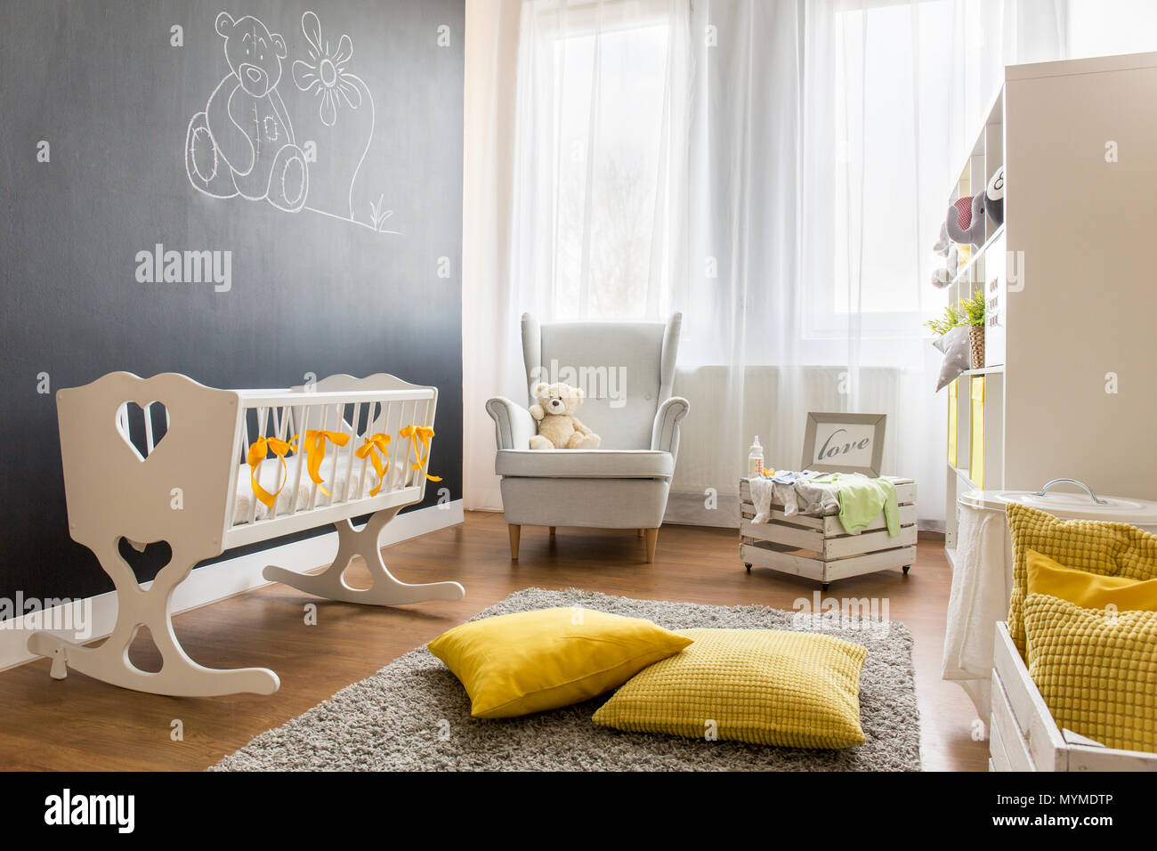 Shot of a spacious modern nursery room with a chalkboard wall - Stock Image