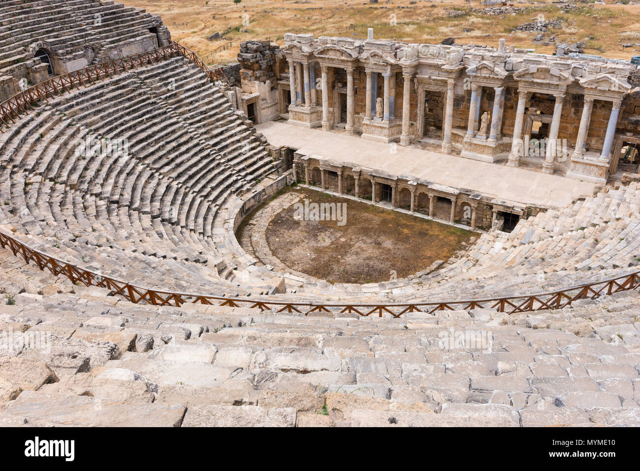 The ancient stone theatre and Greek amphitheatre in Hierapolis near Pamukkale in Turkey now a UNESCO World Heritage Site viewed looking down from the  - Stock Image