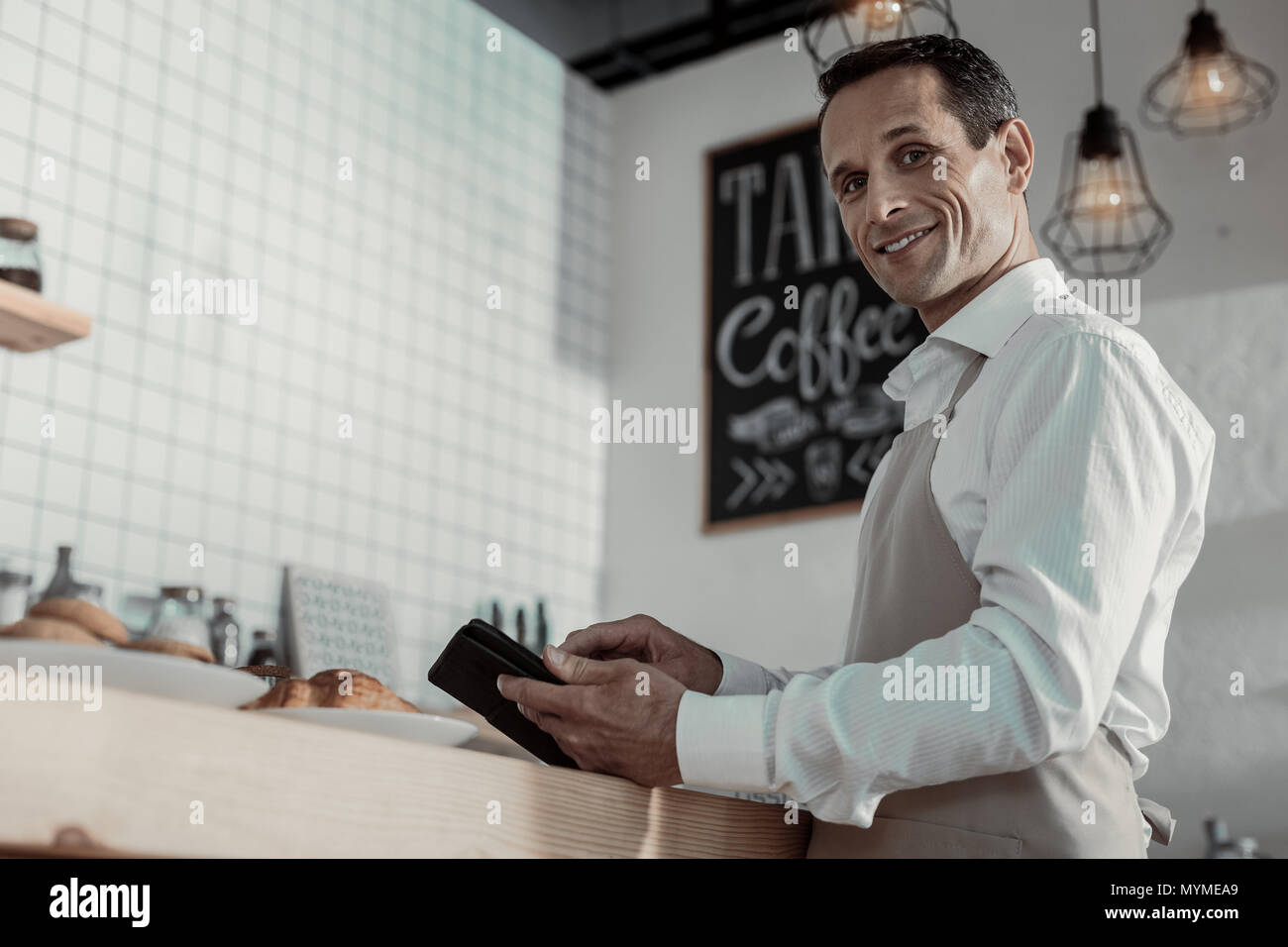 Joyful waiter standing in semi position - Stock Image