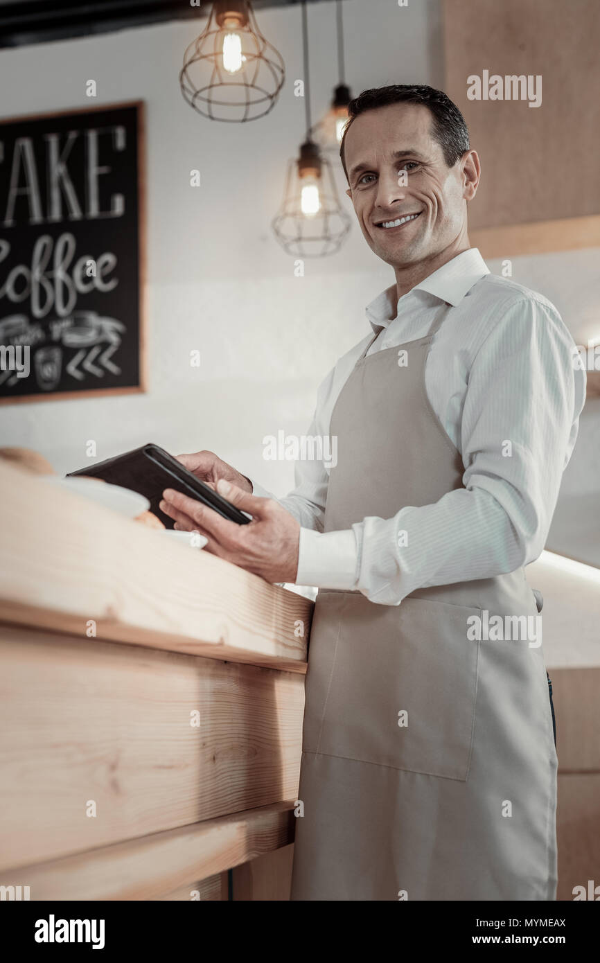 Cheerful male person using his gadget - Stock Image