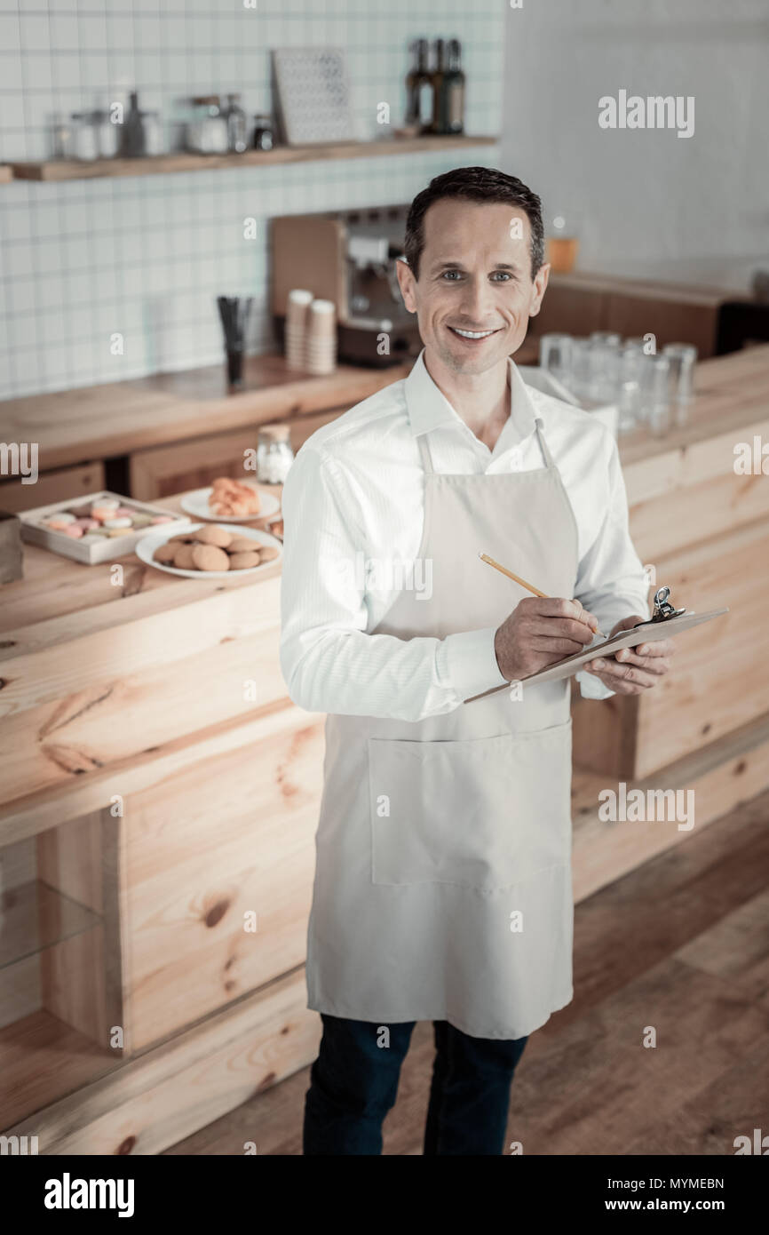 Joyful brunette working in his cafe - Stock Image