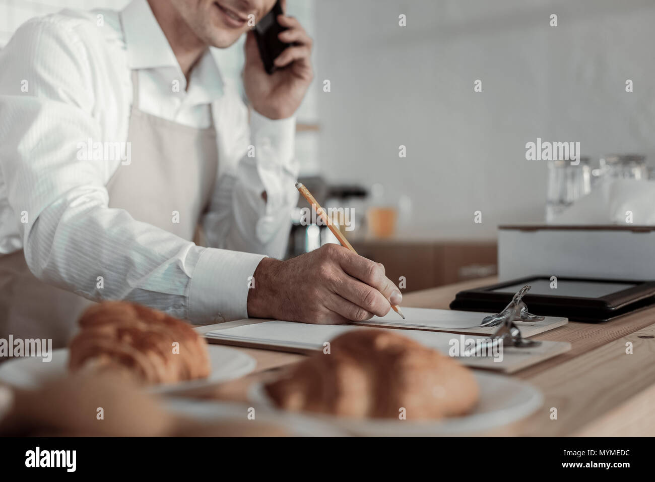 Competent businessman taking order per telephone - Stock Image
