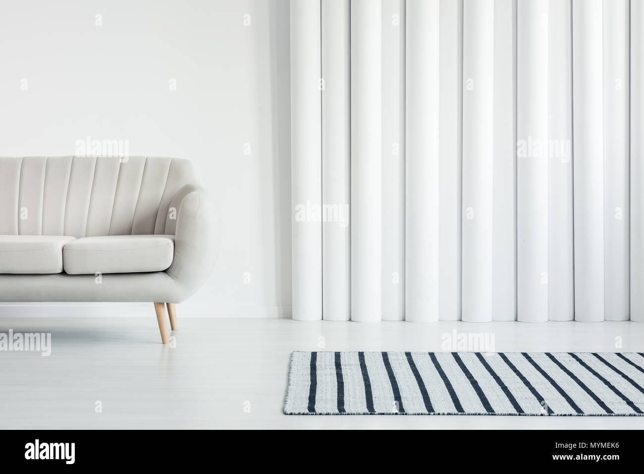 Beige sofa in white living room interior with striped rug and tubes ...