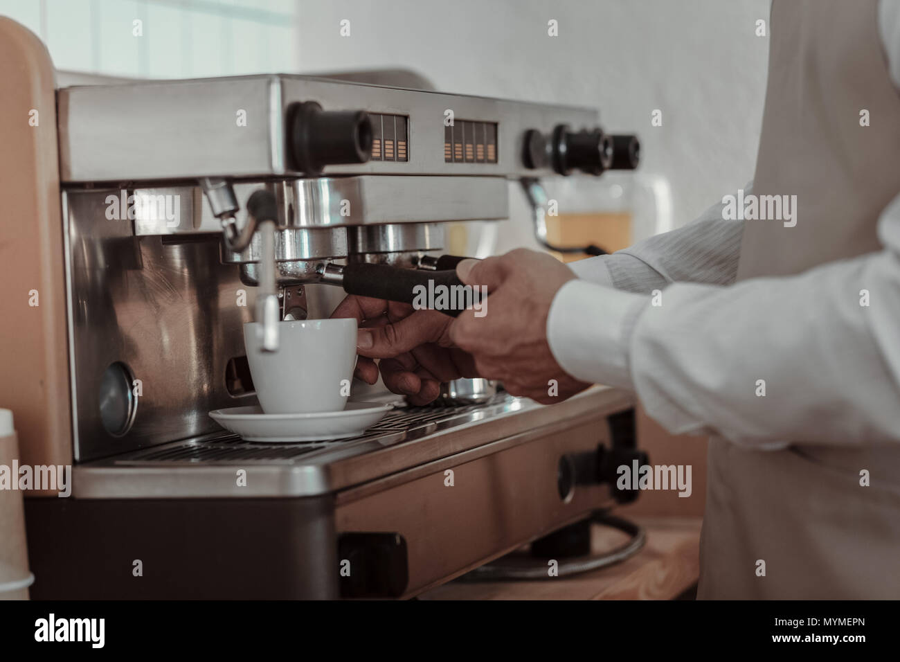 Close up of male hands that using coffee-engine - Stock Image