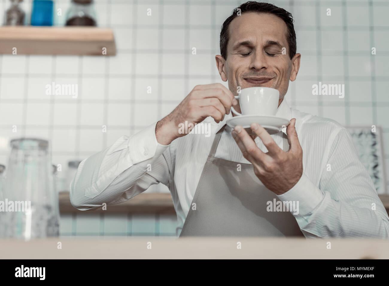 Delighted brunette enjoying morning coffee - Stock Image