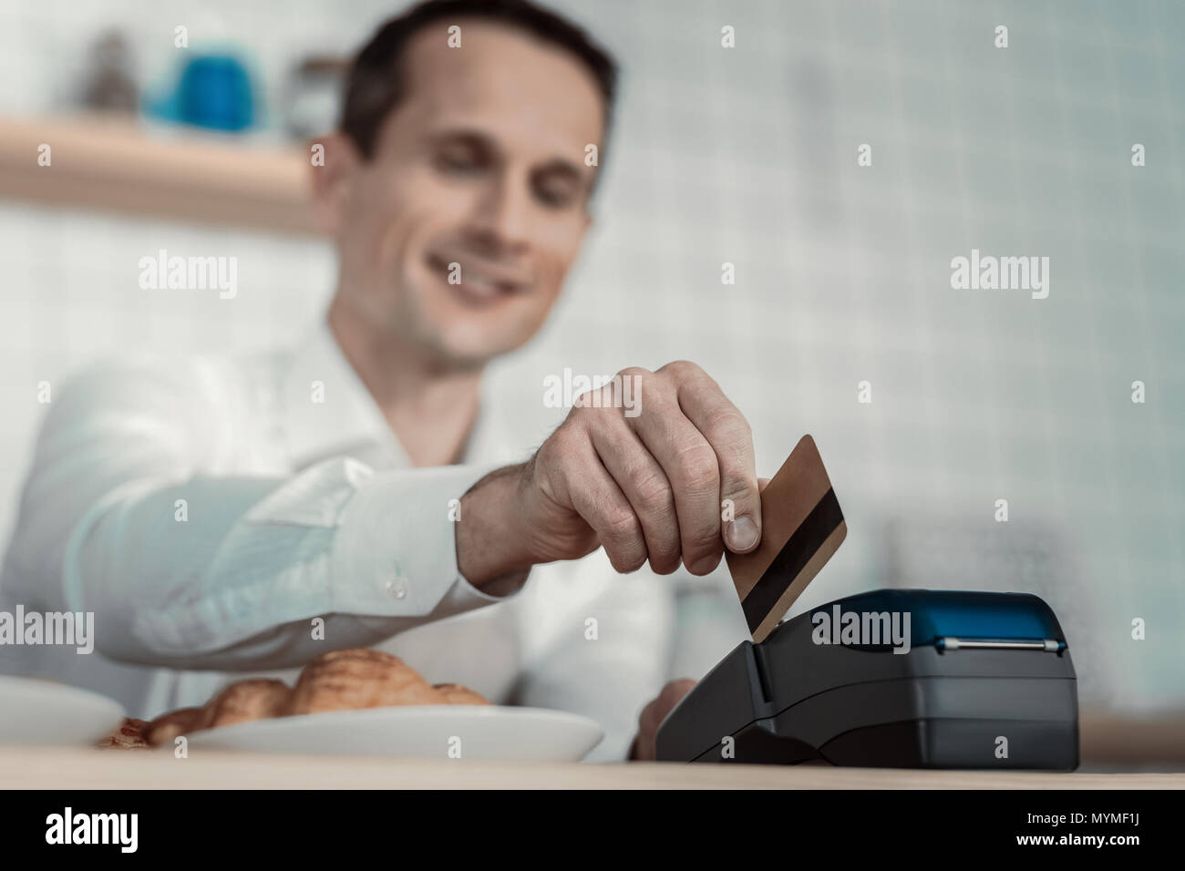 Pleased waiter transferring money into account - Stock Image