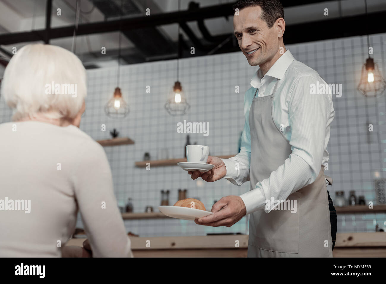 Positive delighted waiter serving his visitor - Stock Image