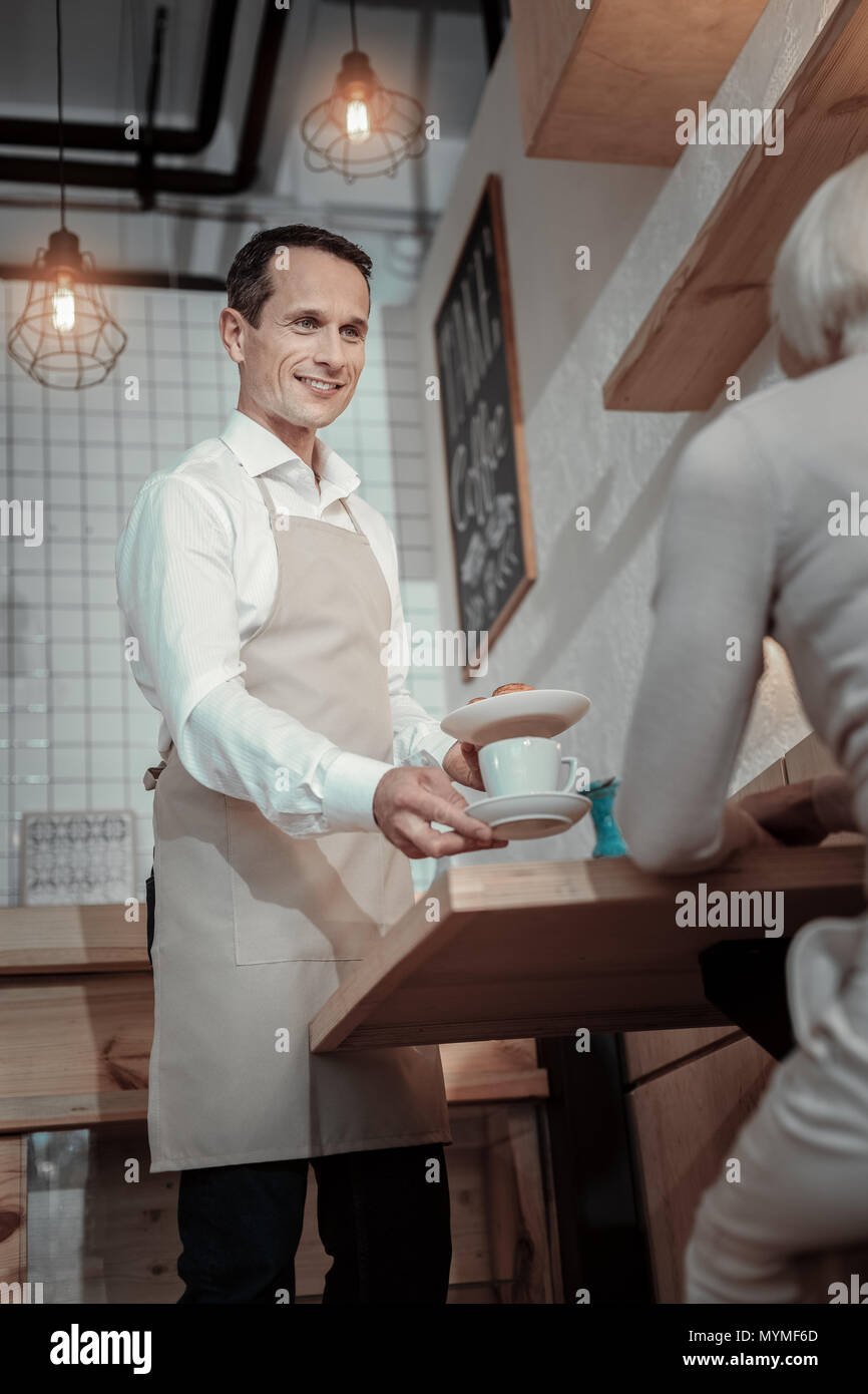 Handsome waiter communicating with his client - Stock Image