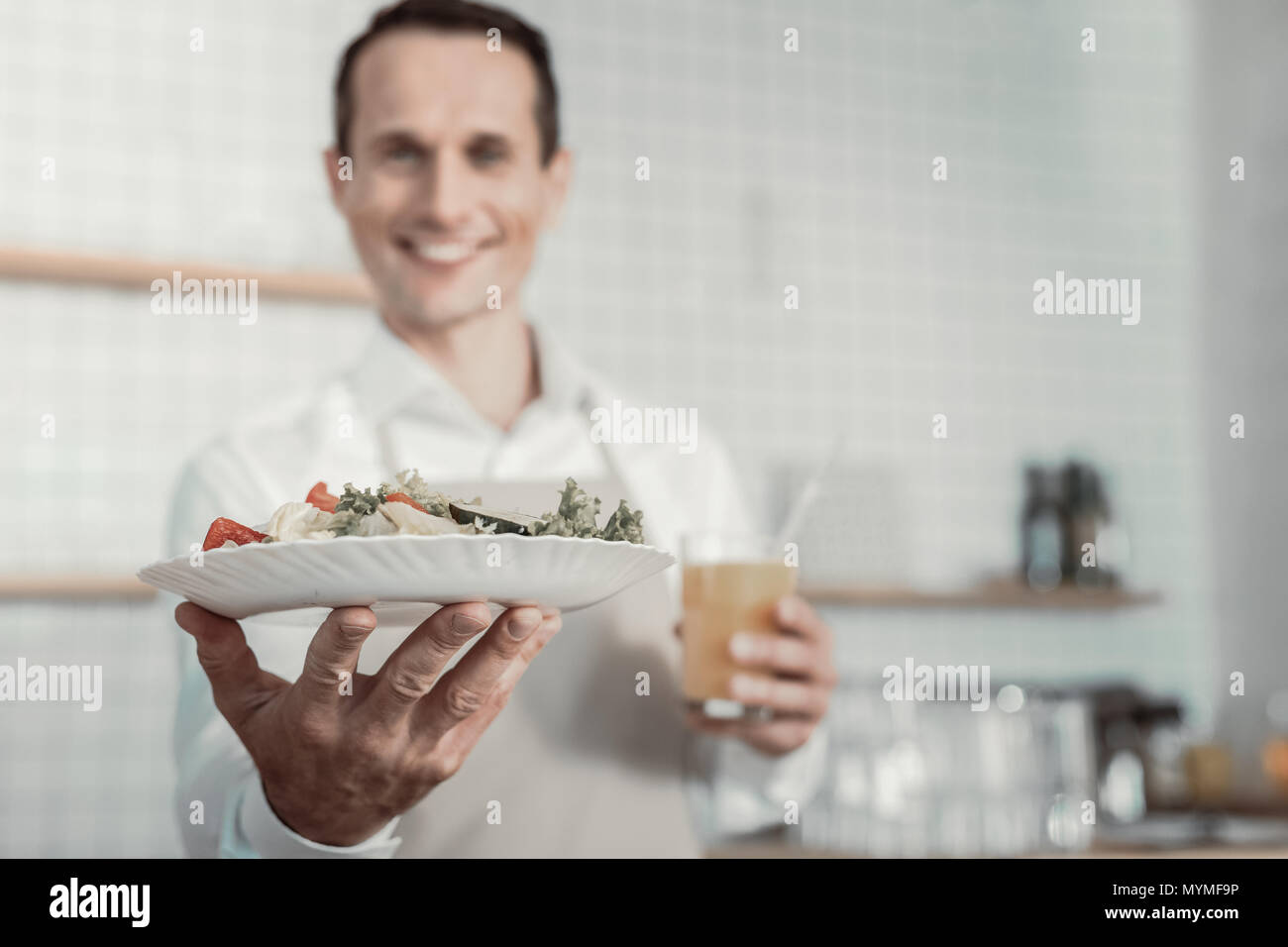 Focused photo on male hand that demonstrating salad - Stock Image