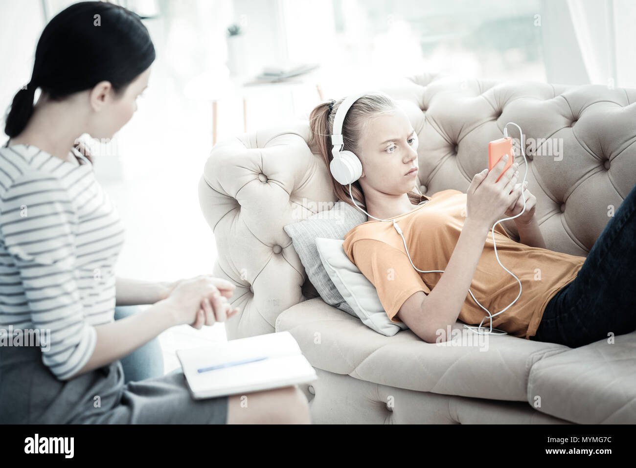 Unpleased teen girl listening to music during therapy - Stock Image