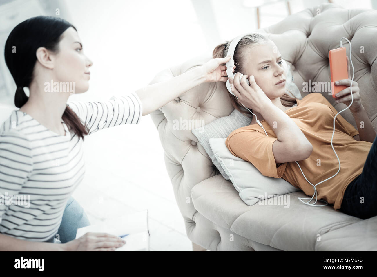 Mad teen girl immersing in music during therapy - Stock Image