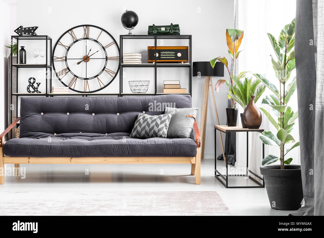 Black wood and leather couch with a patterned cushion standing in bright living room interior with clock on the wall Stock Photo