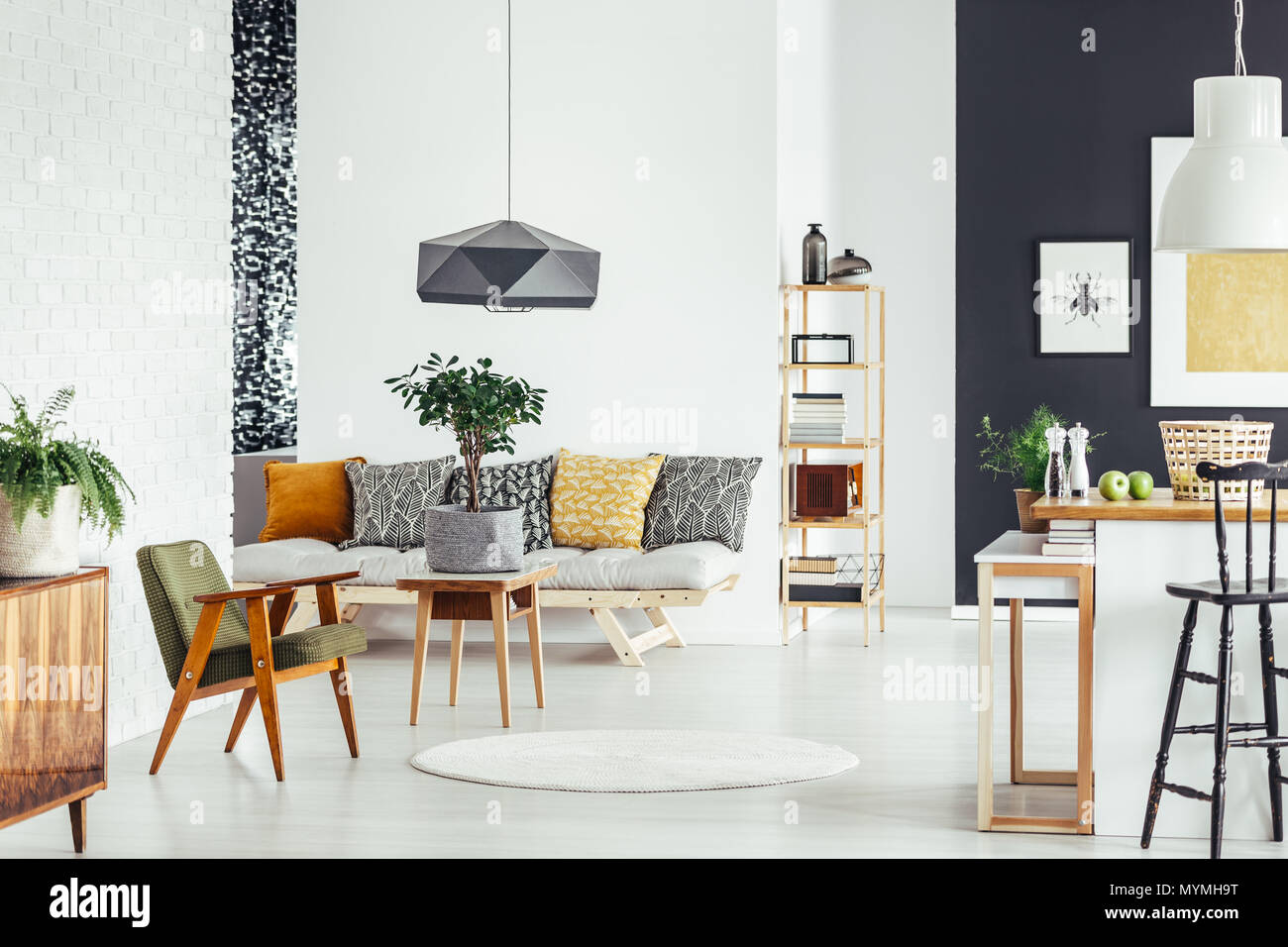 Small tree in material pot on wood table next to vintage green chair in room with patterned pillows on sofa Stock Photo