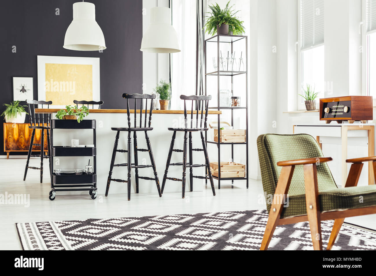 Rustic Green Chair On Black And White Geometric Carpet In Kitchen With Bar Stools At Countertop Stock Photo Alamy