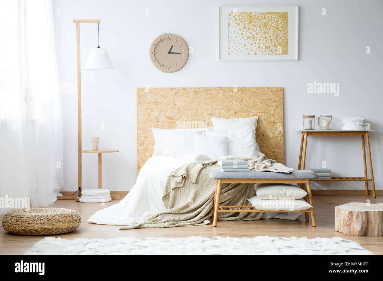 Paper Clock And Gold Painting On The Wall Above Bed With Beige Bedsheets In Bedroom With Pouf And Wooden Furniture Stock Photo Alamy