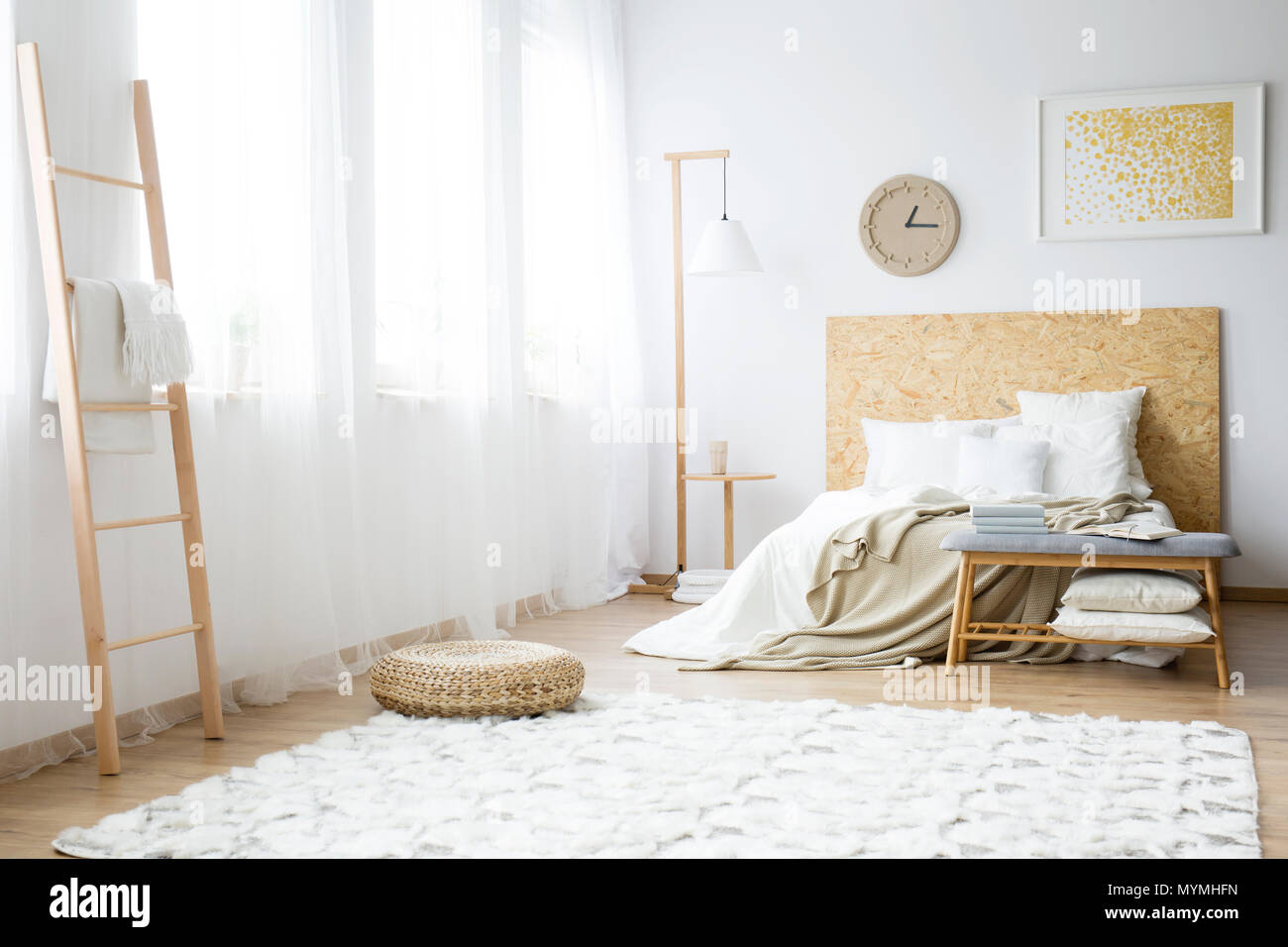 Modern clock hanging over a double bed filled with pillows in a white bedroom interior - Stock Image