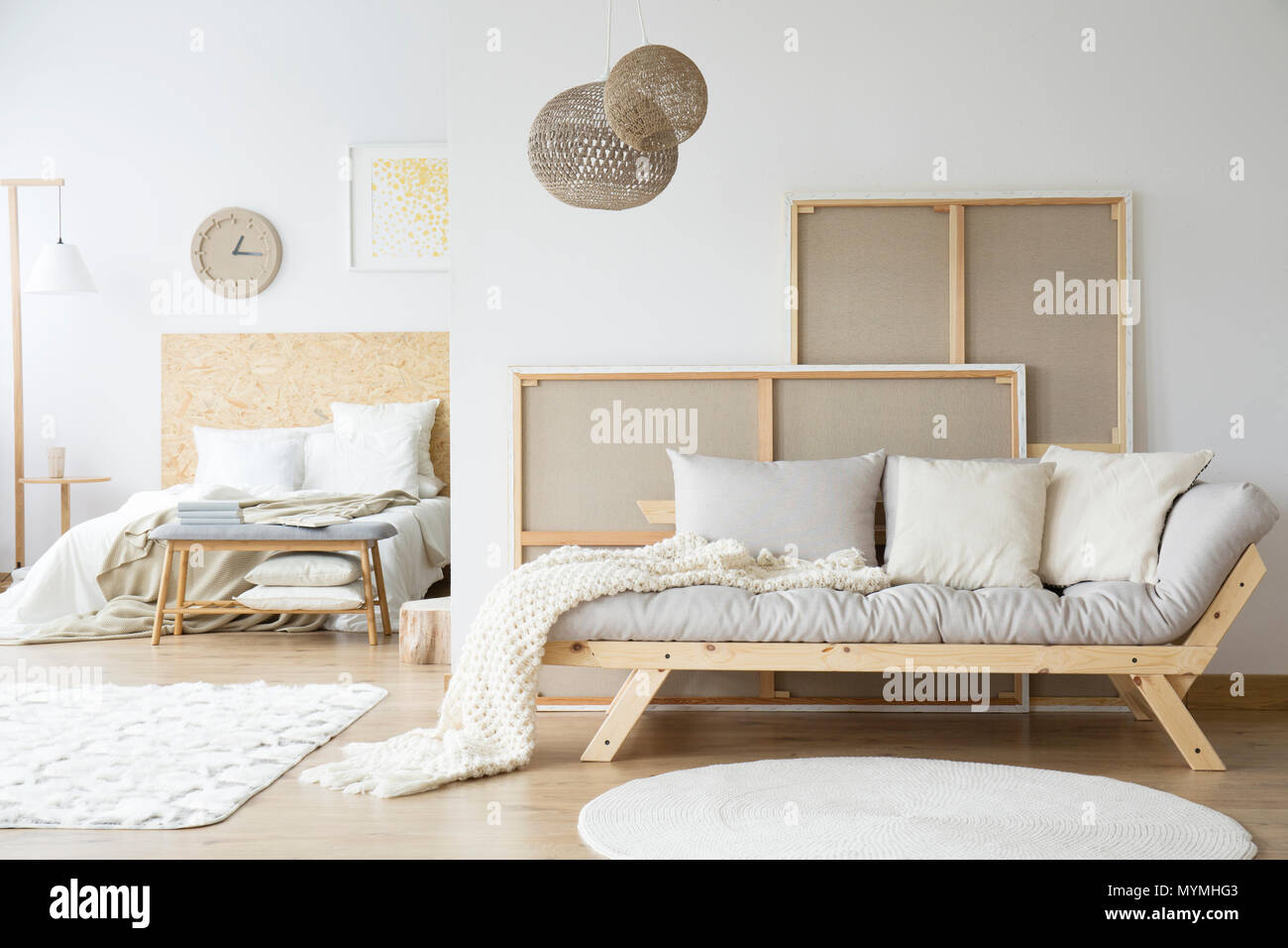 Kings-size bed and a cozy sofa in a monochromatic white room interior - Stock Image