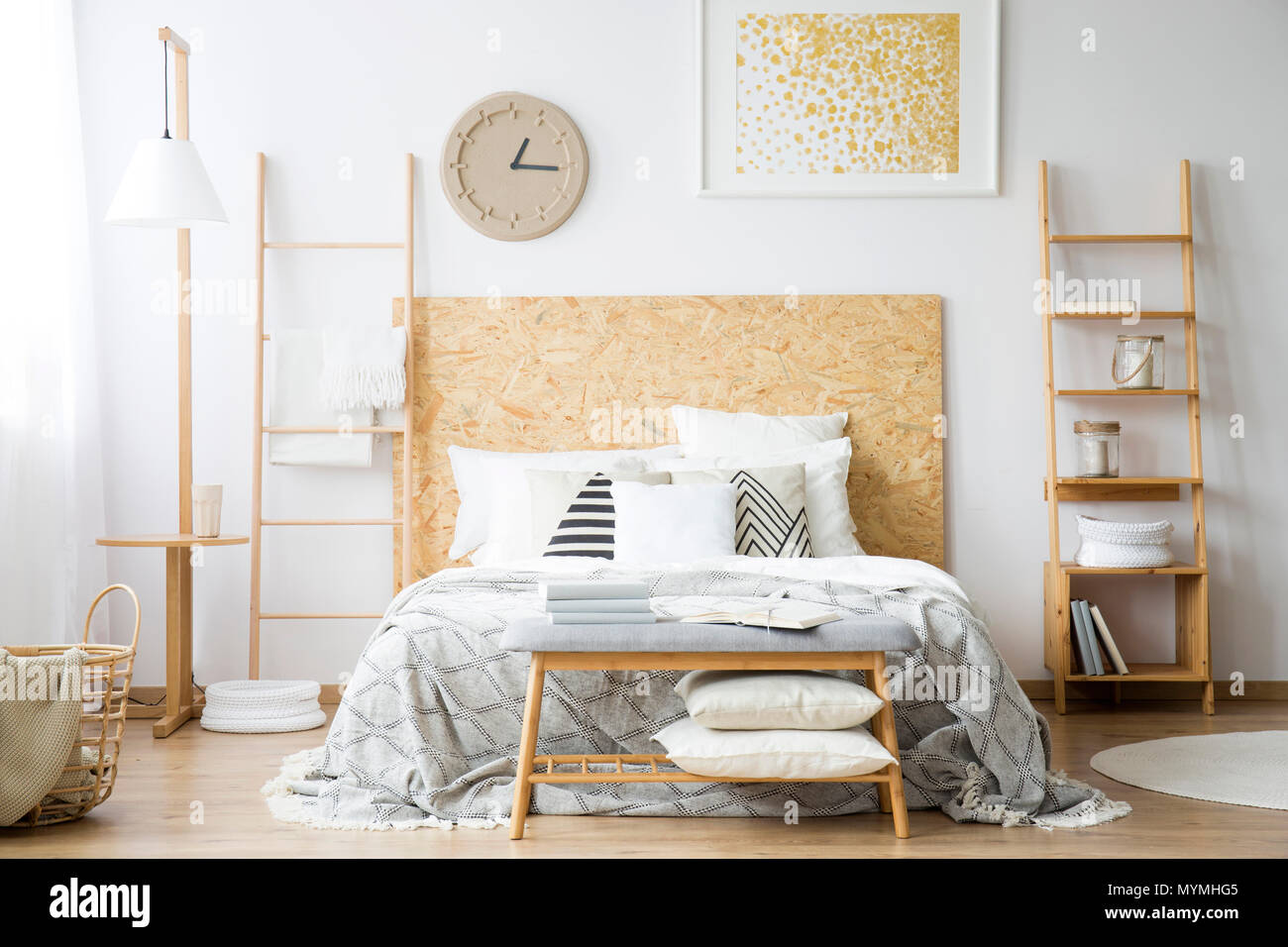 Comfy double bed standing in between two ladders in a monochromatic bedroom interior - Stock Image