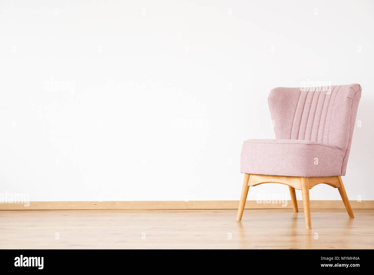 Pink armchair against white wall with copy space in empty living room - Stock Image