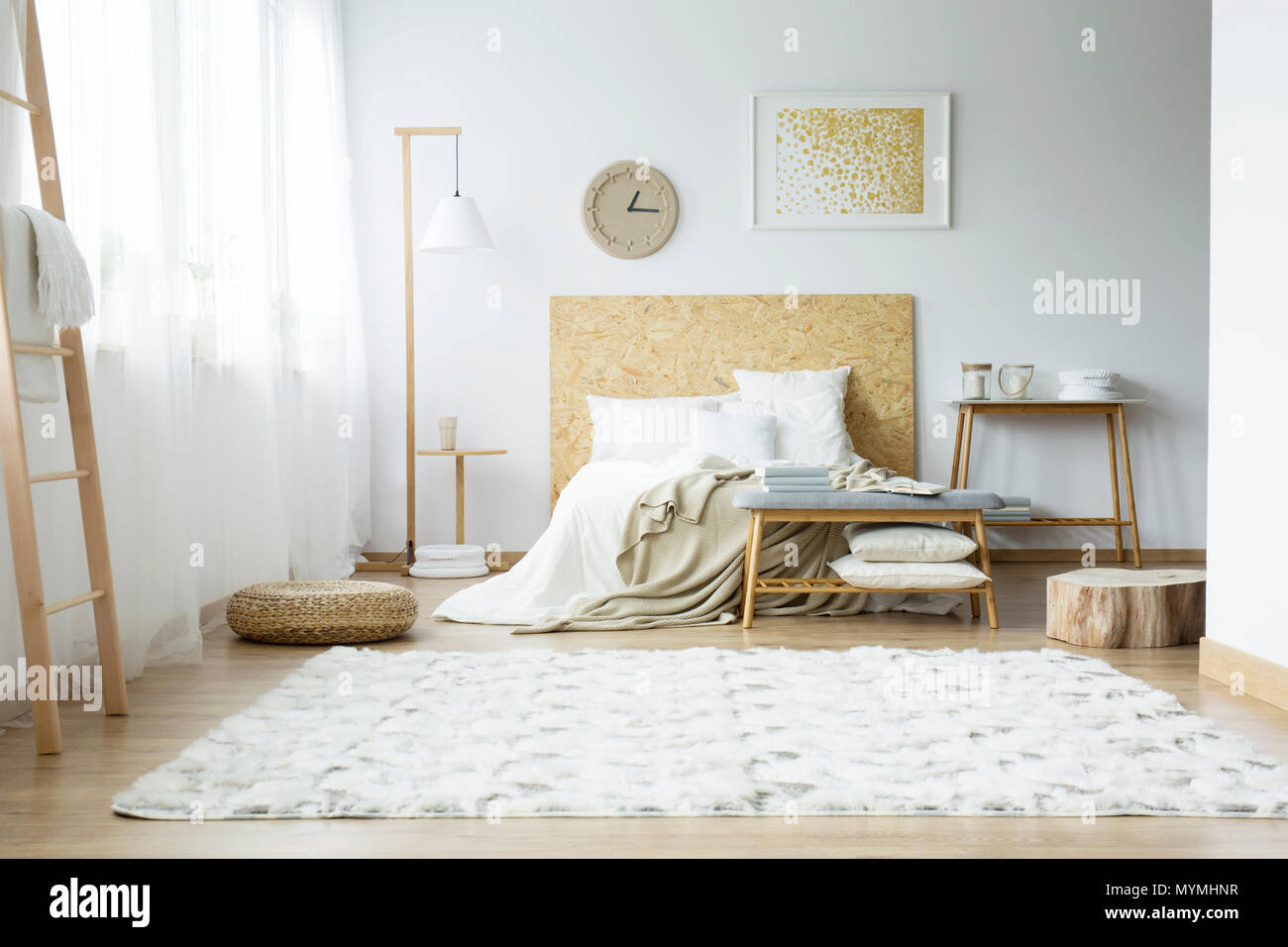 Bright carpet, pouf and wooden stump in spacious bedroom with gold painting above bed near lamp - Stock Image