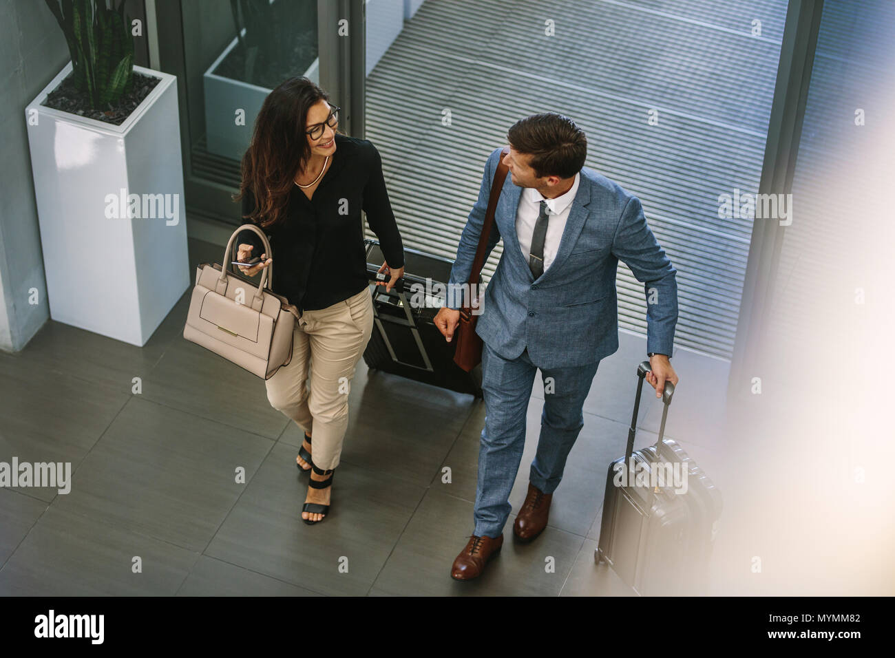 Businessman and woman walking together with baggage and talking. Business people arriving for conference. - Stock Image