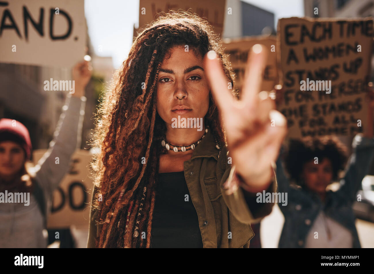 Woman showing a peace sign during protest. Woman with group of females protesting outdoors on city street. - Stock Image
